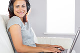 Cheerful casual woman listening to music and using her notebook