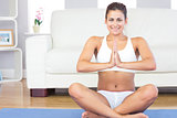 Cheerful young woman sitting in lotus position on a blue exercise mat