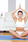 Cute fit woman practising yoga in her living room