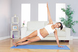 Sporty woman doing yoga pose on exercise mat