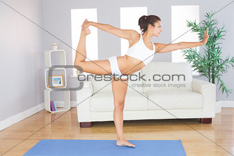 Slim woman stretching her body standing on an exercise mat