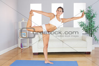 Portrait of young slim woman stretching her body with yoga exercise