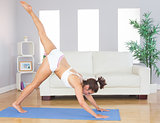 Sporty woman stretching her body with yoga pose on an exercise mat