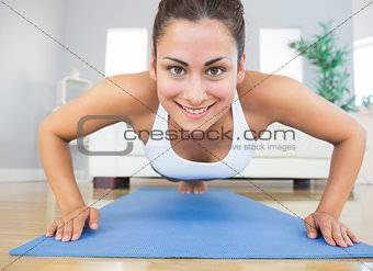 Fit young woman practicing press ups on a blue exercise mat