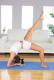Profile view of slim woman practicing yoga pose on exercise mat