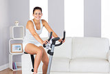 Joyful slim woman smiling at camera while training on an exercise bike