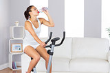 Lovely slender woman drinking while training on an exercise bike