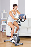 Content slim woman using her tablet while training on an exercise bike