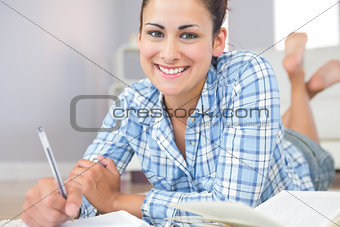 Portrait of beautiful young student doing assignments lying on the floor