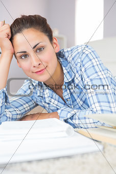 Portrait of calm young student doing assignments while lying on the floor