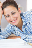 Pretty brunette student smiling at camera while lying on the floor in front of assignments