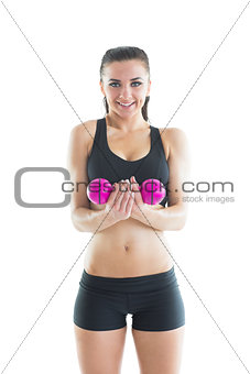 Portrait of happy active woman training using a pink dumbbell