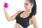 Natural active woman training with pink dumbbells