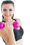 Joyful attractive woman smiling at camera while training with a dumb-bell