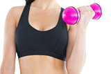 Close up of sporty young woman training with a pink dumbbell