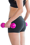 Mid section of sporty young woman holding pink dumbbells