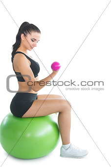 Attractive young woman sitting on an exercise ball using pink dumbbells