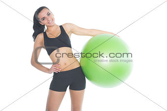 Attractive fit woman posing holding a green exercise ball