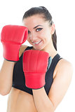 Joyful brunette woman wearing boxing gloves smiling at camera