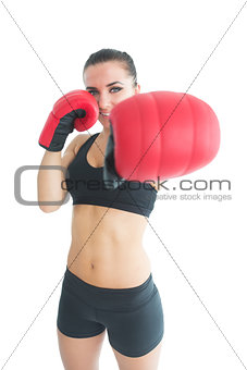 Beautiful sporty woman posing wearing red boxing gloves