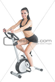 Cheerful ponytailed sporty woman training on an exercise bike
