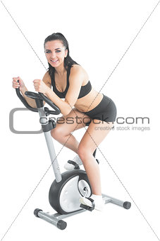 Beautiful ponytailed woman using her exercise bike