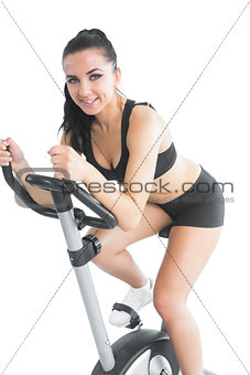 Beautiful brunette woman training with an exercise bike