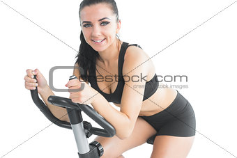 Attractive sporty woman exercising with an exercise bike
