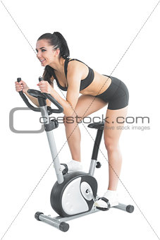 Active ponytailed woman training on an exercise bike