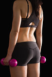 Rear view of slender woman holding pink dumbbells