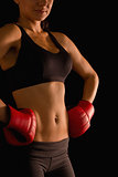 Mid section of young sporty woman posing and wearing boxing gloves