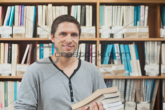 Attractive mature student standing in a library holding some books