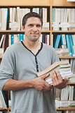 Mature student posing in library holding a pile of books