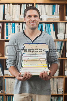 Adult student posing holding a stack of books