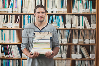 Attractive librarian holding a pile of books standing in library