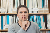 Brunette male librarian requesting silence in library