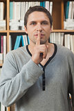 Male librarian making a sign to be quiet in library