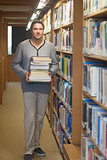 Attractive male librarian carrying a pile of books