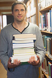 Handsome brunette librarian posing in library holding a pile of books