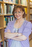 Mature female librarian posing in library with crossed arms