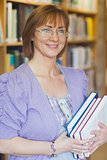 Female librarian posing holding some books