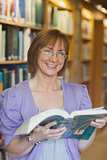 Cheerful mature female librarian posing holding an opened book