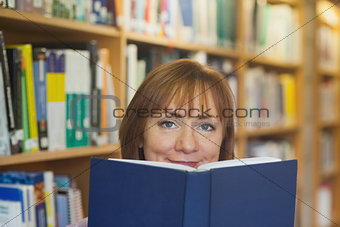 Peaceful mature woman holding a book in a library