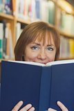Content mature woman sitting in library holding a book