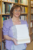 Mature female librarian posing holding a pile of books