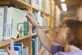 Mature female librarian searching a book