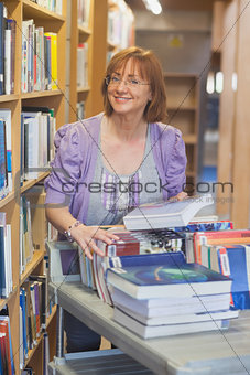 Female mature librarian returning books in library