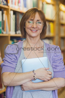 Mature female librarian posing in library holding a tablet
