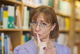 Mature female librarian giving a sign to be quiet standing in library