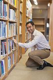 Young attractive man cowering in front of bookshelves